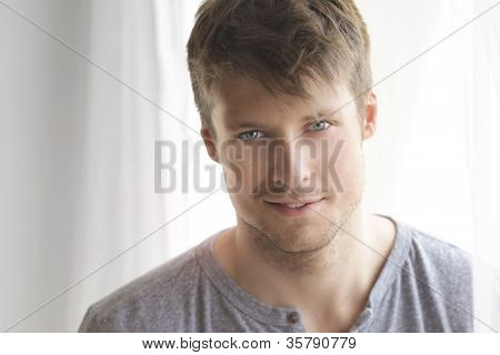 Intimate portrait of a beautiful young man with nice relaxed smile and sparkling blue eyes near window