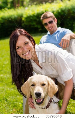 Happy young couple sitting with golden retriever dog in park