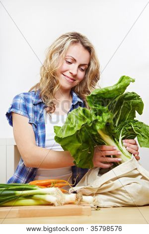 Happy woman in kitchen with shopping bag full of vegetables