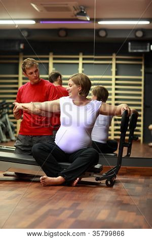 Physical therapist stretching happy,pregnant woman's arm in gym