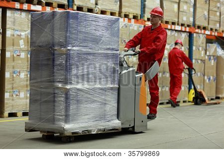 Warehousing -  Two workers in uniforms and safety helmets working in storehouse