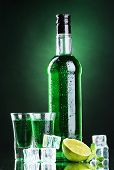 stock photo of absinthe  - bottle and glasses of absinthe with lime and ice on green background - JPG