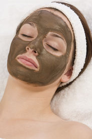 stock photo of mud pack  - A beautiful young brunette woman rests after having a chocolate face mask applied by a beautician - JPG