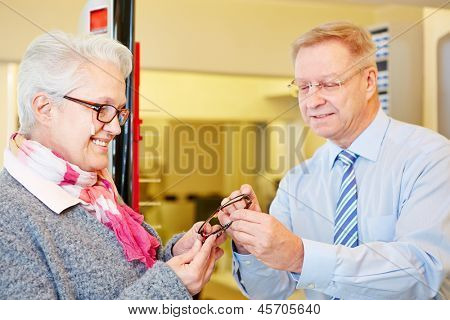 Happy senior woman buying new glasses at the optician