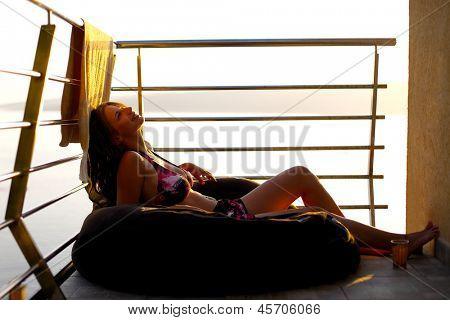 Young woman sunbathing on the balcony