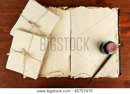 Open old book, letters and ink pen on wooden background