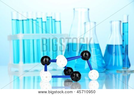 Molecule model and test tubes with liquid on blue background