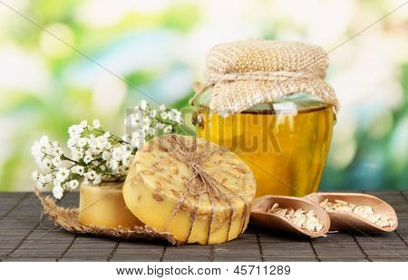Hand made soap and ingredients for soap making on bamboo mat, on green background