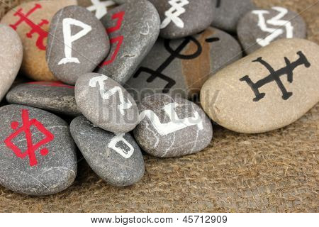 Fortune telling  with symbols on stones on burlap background