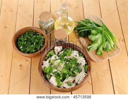 Boiled meat on wooden bowl and herbs on wooden table