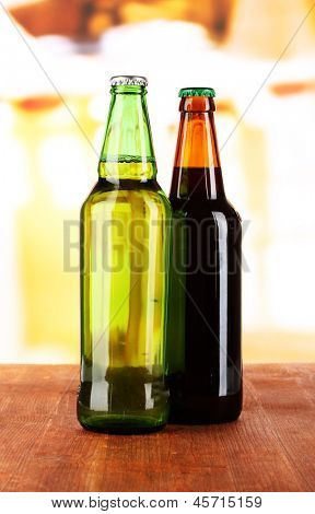 Bier in bottles on table on room background