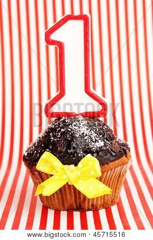 Birthday cupcake with chocolate frosting on striped background
