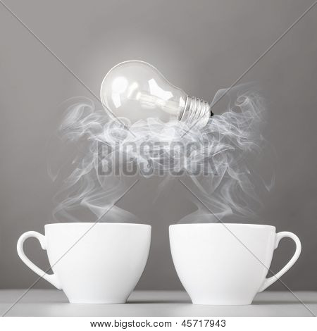 idea birth. bulb is lying on steaming hot coffee cups