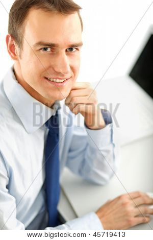 Portrait of a happy young businessman sitting on the desk, isolated on white background