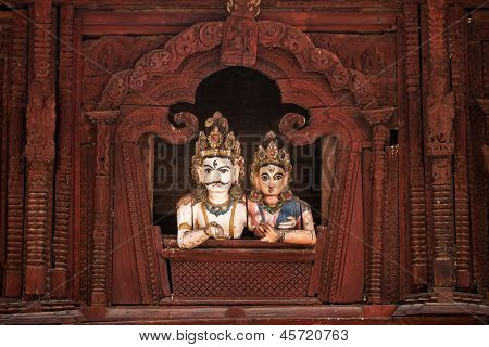 Shiva and Parvati wooden figures in the window of Shiva Parvati Hindu temple at Durbar Square in Kathmandu, Nepal