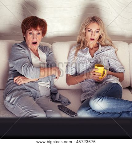 Mother with adult daughter watching television. Women looking film thriller