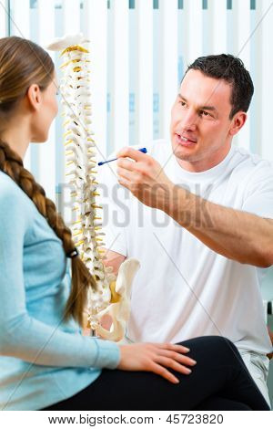 Physiotherapist in his practice, he explains a female patient the vertebral column and the emergence of back pain