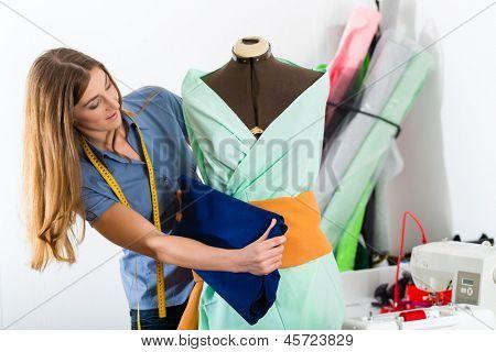 Freelancer - Fashion designer or Tailor working on a design or draft, she takes measure on a dressmakers dummy