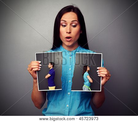 amazed woman looking at disrupt photo of couple in quarrel