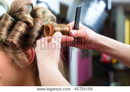 Hairdresser - hair stylist curling hairs, a female customer gets a haircut