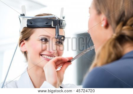 Doctor - Young female doctor or ENT specialist - with a patient in her practice, examining the throat with a spatula