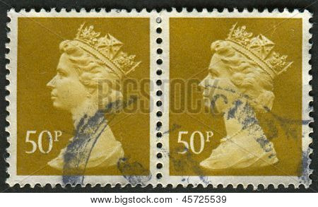 UK-CIRCA 1977: A stamp printed in UK shows image of Elizabeth II is the constitutional monarch of 16 sovereign states known as the Commonwealth realms, in Ochre Brown, circa 1977.