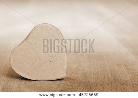 heart shaped box on wooden table, sepia toned
