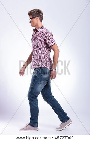 side view of a casual young man walking forward, away from the camera. on gray background