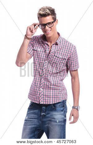 casual young man holding his hand on his eyeglasses, while smiling to the camera. on white background