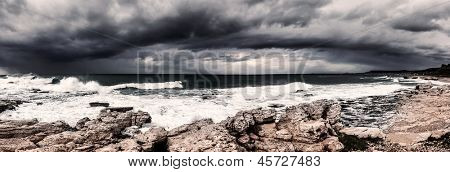 Landscape of storm on the sea, dark cloudy sky, rocky seashore, hurricane in the ocean, rainstorm, wind power, bad weather concept