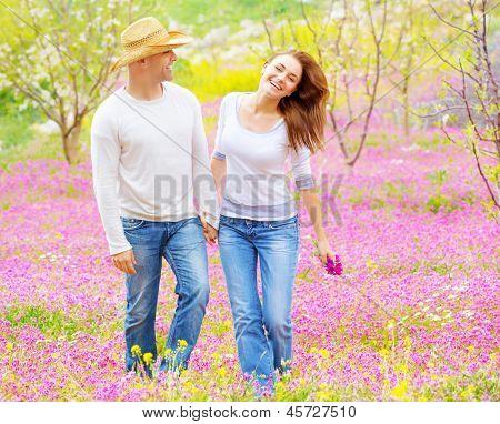 Mooie gelukkige paar genieten van voorjaar aard, lachen en plezier buiten, wandelen op paarse f