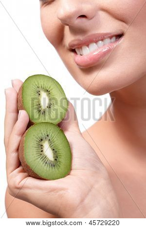 Closeup lips of smiling young healthy woman with kiwifruit in hand.
