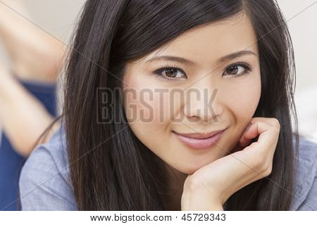 Portrait of a beautiful young Chinese Asian Oriental woman resting on her hand