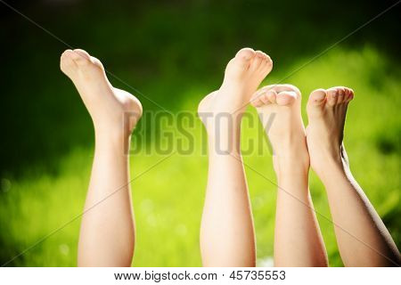 Happy children lying on green grass outdoors in summer park