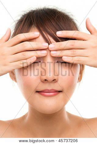Eye massage. Skin care woman putting eye cream touching upper eyes. Facial beauty closeup of beautiful mixed race Asian female model isolated on white background.