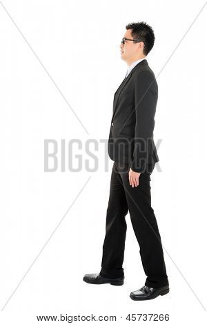 Full body side view of Asian business man walking, isolated on white background