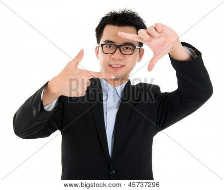 Finger frame. Smiling Asian business man making a frame with fingers, isolated on white background