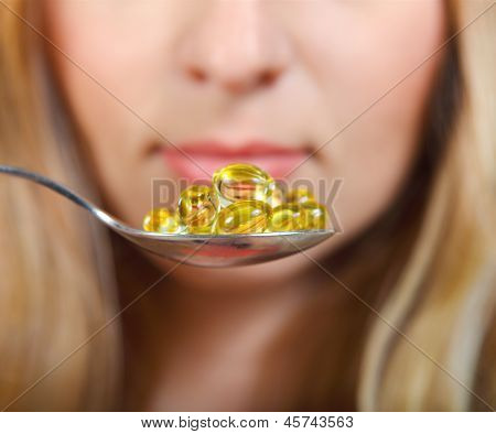 Woman Holding A Spoon Full Of Pills