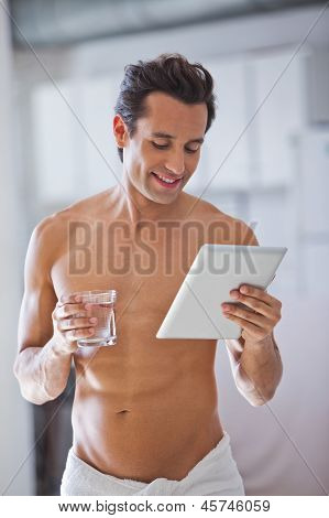 Man Wrapped In Towel Holding A Glass Of Water  And Tablet