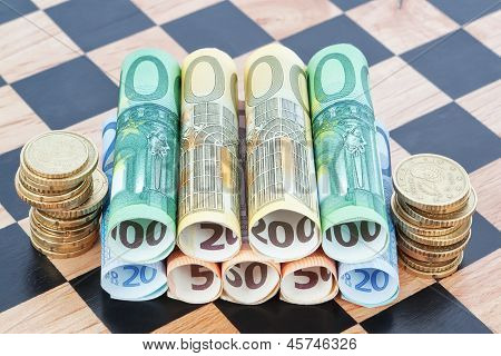 Paper Money And Coins As The Euro On The Chessboard. Concept Image.