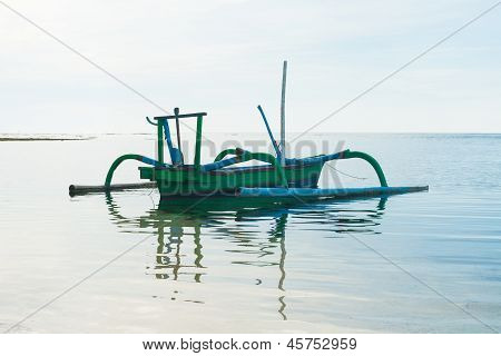 Outrigger boat with reflection