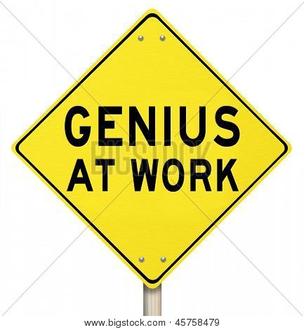 The words Genius at Work on a yellow road sign to give you warning that someone smart, brilliant, intelligent or extremely knowledgable is working on a project or goal