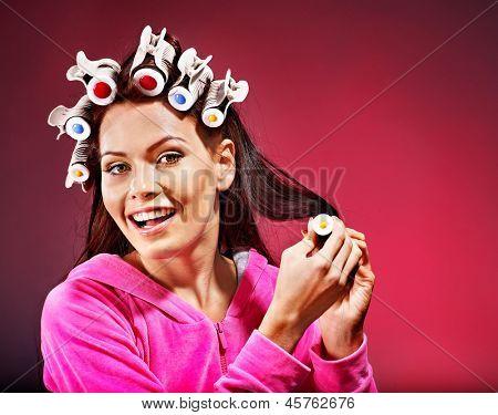 Happy woman wear hair curlers on head.