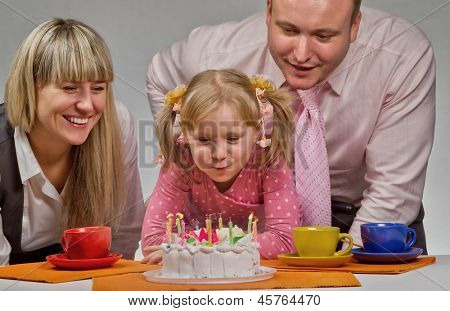 Mother burning candles in her birthday with her happy family