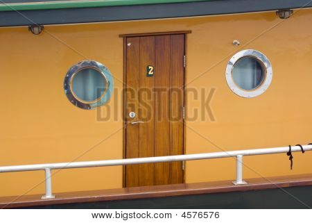 Boat Deck With Wooden Door And Portholes In Brown