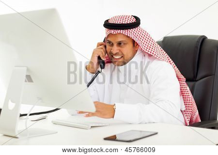 handsome arabian businessman talking on landline phone in office