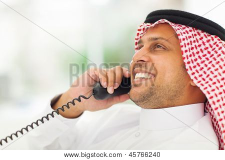 smiling male arabian office worker chatting on the phone