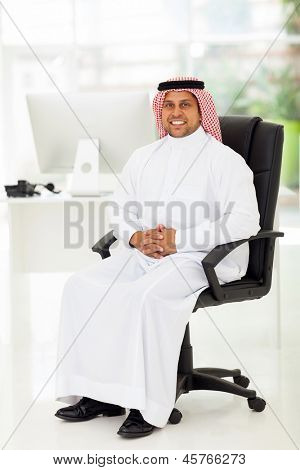 smiling middle eastern businessman sitting in modern office