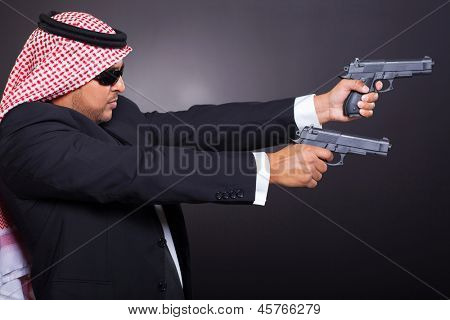 dangerous arabian hit man shooting with two guns over black background