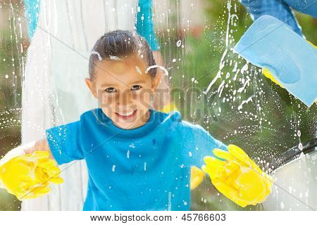 cute little girl cleaning window glass with parents at home
